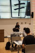Kiri Lee demonstrating how to do calligraphy for ASIA 090 students