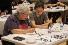 Nicola Tannenbaum and ASIA 090 student practicing calligraphy