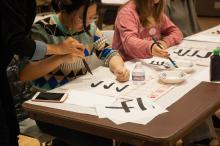Kiri Lee teaching ASIA 090 students how to do calligraphy