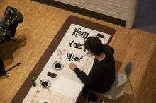 Birds eye view of ASIA 090 students practicing calligraphy